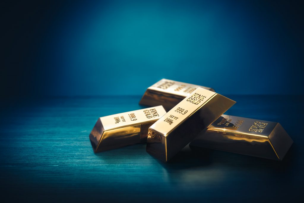Pile of gold bars or ingots on a dark background