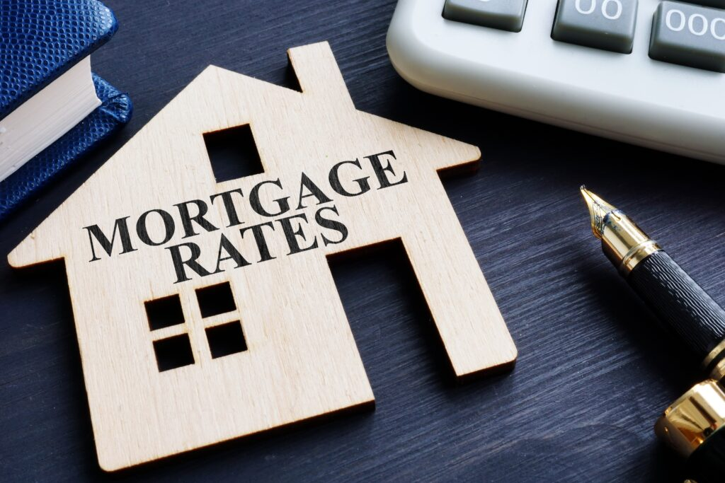 Mortgage rates written on a wooden model of house.
