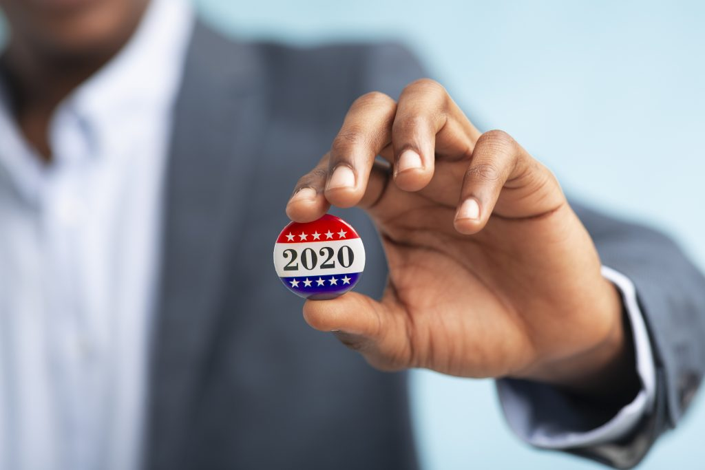 Businessman holding Vote button for Presidential election 2020