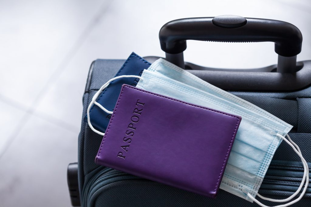 Travel suitcase, passport and medical mask.